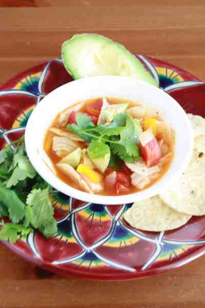 Slow Cooker Chicken Tortilla Soup in a bowl with chips, avocado, and cilantro