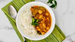 Zucchini, Chickpea, & Potato Curry featured overhead of bowl with curry and rice plus napkin spoon and parsley sprig recipe card image