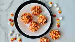 Halloween Popcorn Balls featured overhead of popcorn balls on a plate and some to the side with marshmallows and candy corn on the counter