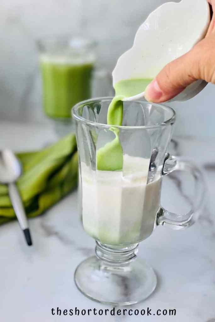 iced Matcha Latte (Starbucks Copycat) pouring matcha into the glass filled with cream and ice