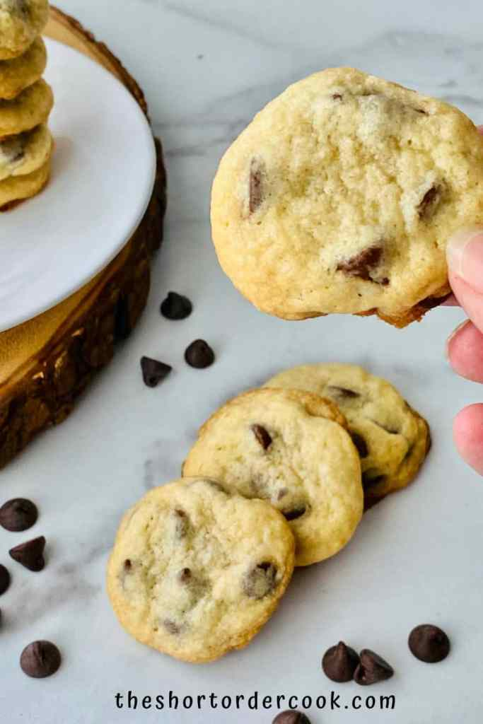 Chocolate Chip Cookies without Brown Sugar cookies ready to eat fanned on the marble counter and a hand holding one up close