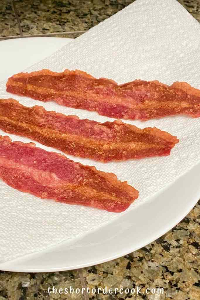 How to Cook Turkey Bacon in the Microwave Oven 3 cooked strips on a plate with paper towels