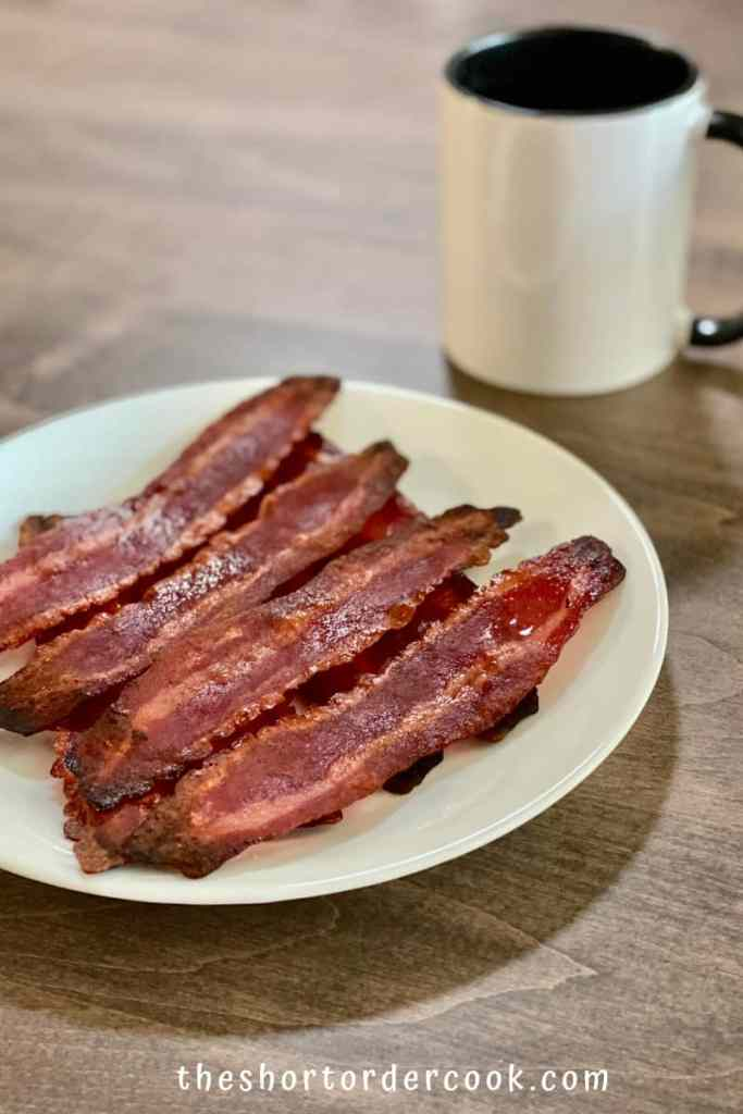 How to Cook Turkey Bacon in the Microwave Oven ready to eat on a plate with a mug in the background