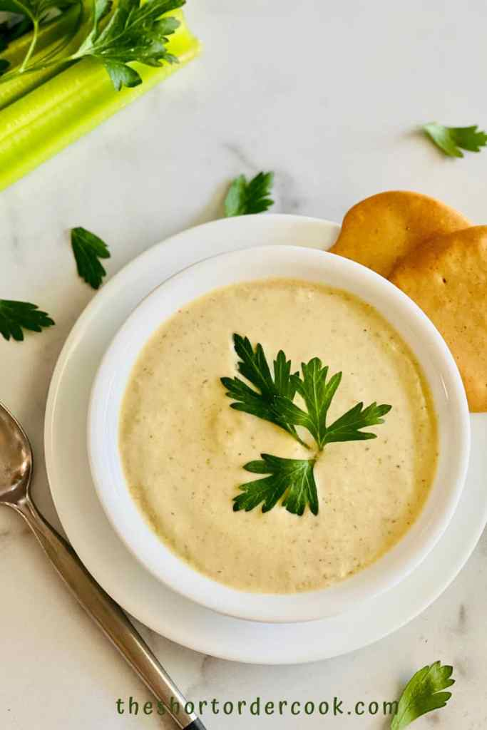 Instant Pot Cream of Celery Soup ready to eat in a bowl with crackers and a spoon on the table and celery stalks and parsley in the background