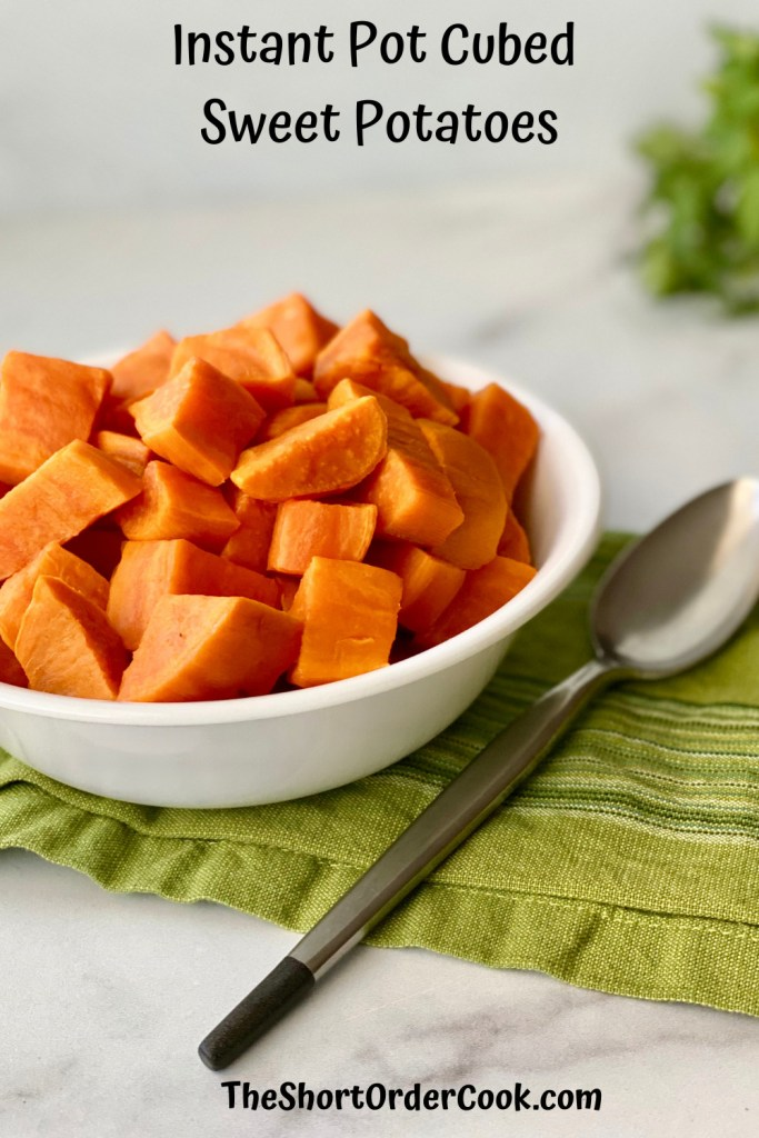 Instant Pot Cubed Sweet Potatoes PN1 a bowl filled with cooked sweet potato cubes plus a spoon and green napkin