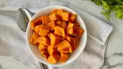 Instant Pot Cubed Sweet Potatoes featured overhead of a bowl filled with cubed sweet potatoes a spoon white linen cloth and fresh parsley