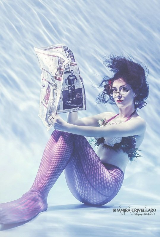 mermaid reading a newspaper underwater wearing glasses