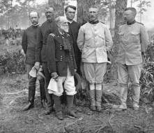 "Lt. Col. Roosevelt and Col. Leonard Wood standing with officers of the 1st U.S. Cavalry. Maj. Gen. Joseph Wheeler (front), a veteran of the Civil War, excitedly mistook the enemy as ""the damn Yankees"" at Las Guásimas. (Florida Memory)"