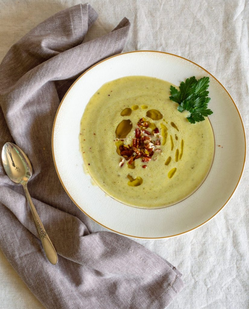 zucchini soup in a white bowl with a grey napkin and silver spoon.