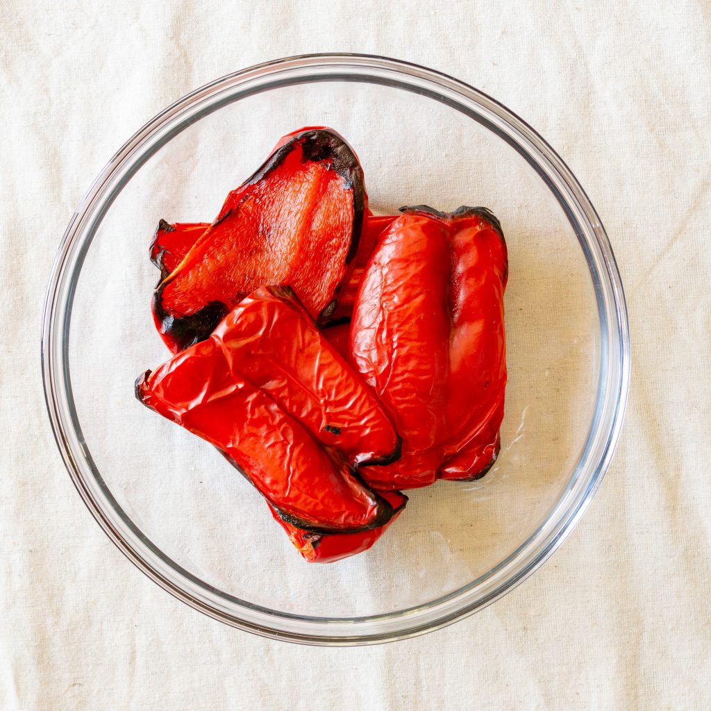 Roasted red peppers in a glass bowl.