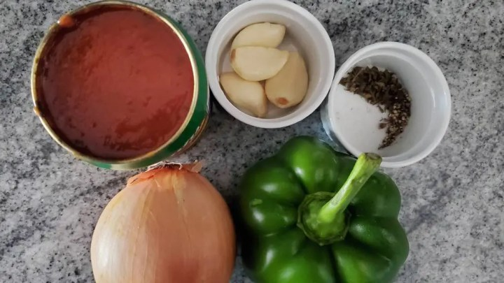 The ingredients used in this recipe are hot dogs, hot dog buns, green pepper, onion, garlic, tomato sauce, salt, pepper and oregano.