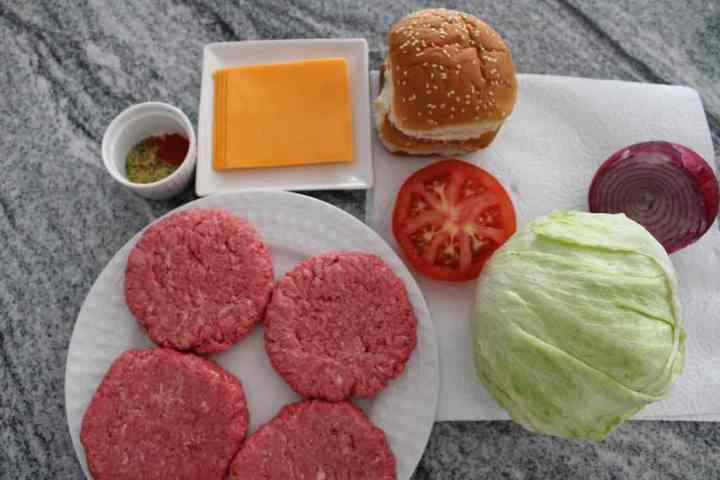 The ingredients to make instant pot hamburgers include ground beef, salt, pepper, smoked paprika, granulated garlic, cheddar cheese, lettuce, tomato, onions and ketchup.