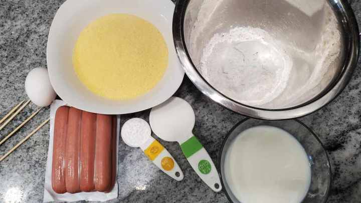 The ingredients to make air fryer corn dogs are corn meal, flour, egg, milk, hot dogs, baking powder, sugar and salt.