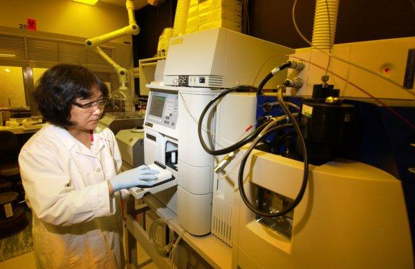 scientist operating high performance liquid chromatography machine