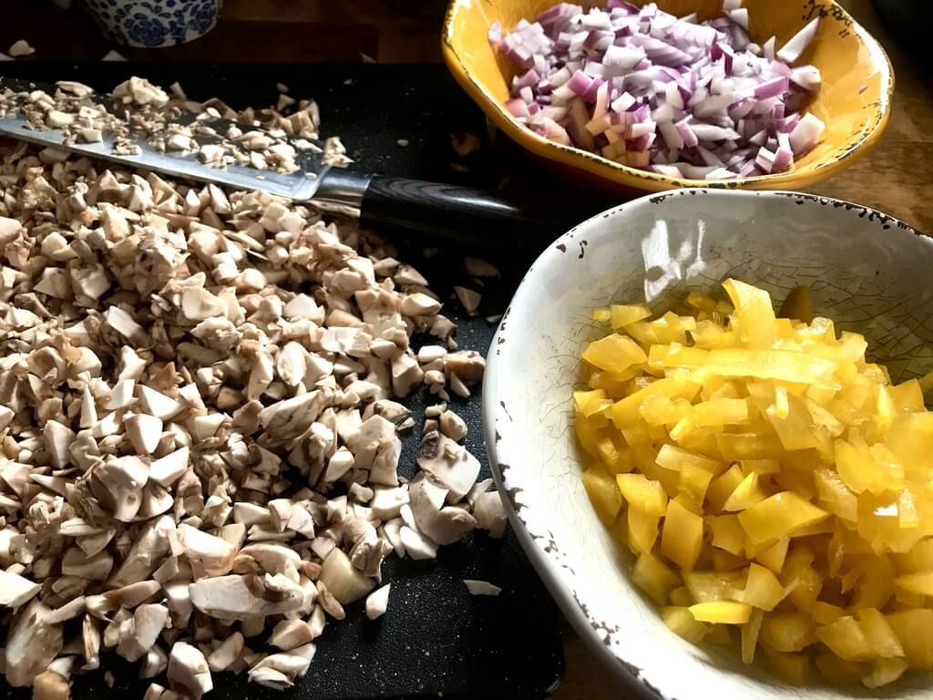 Chopped mushrooms on a cutting board alongside two bowls: one containing chopped yellow peppers, the other chopped onions.