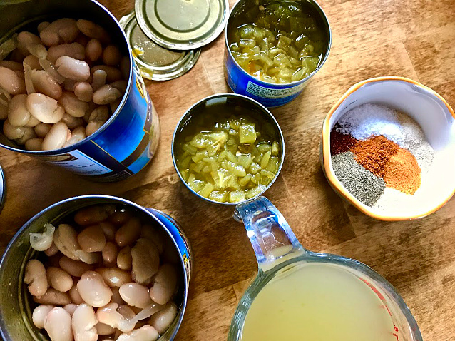 An overhead view of our ingredients: 2 cans of Great Northern Beans, 2 small cans of Diced Green Chilies, chicken broth, and a small ceramic bowl containing a colorful mix of the different spices.
