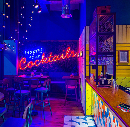 Bar area of Las Iguanas in Bracknell with seating area to the left and bright neon cocktail sign