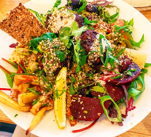 Pumpkin falafel balls served with mixed salad, quinoa, beetroot, roasted parsnips, hummus, pickles and olives with a seeded crispbread and slice of lemon.