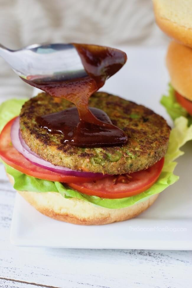 Spreading barbecue sauce on a vegetarian burger