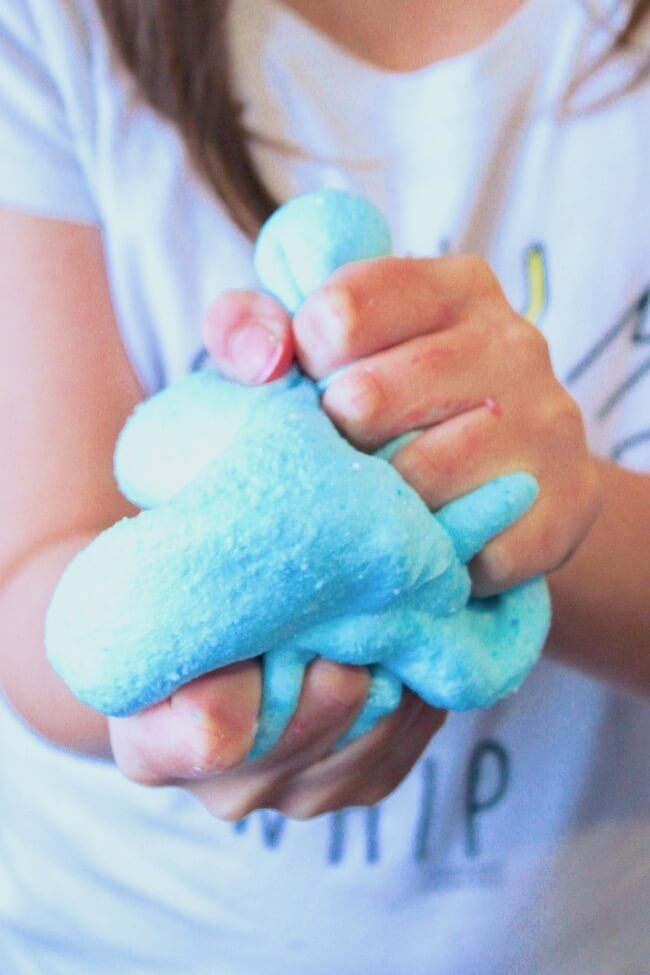 Squishing blue cotton candy slime in hands