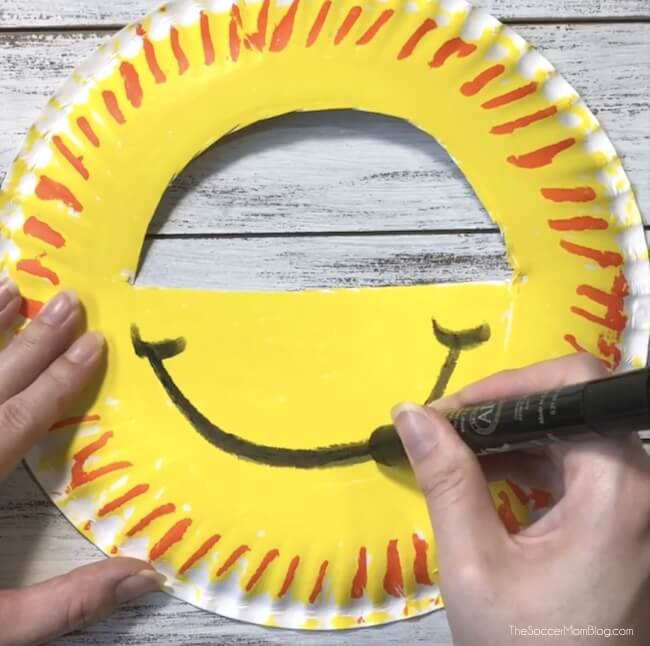 Drawing a smiley face on a paper plate