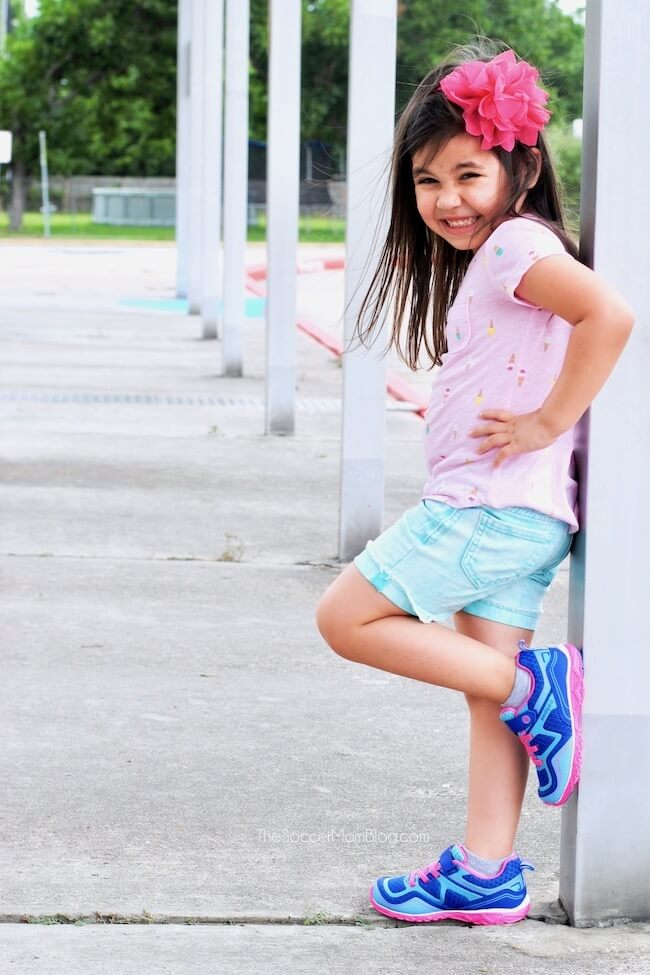 little girl leaning on railing with bright blue shoes