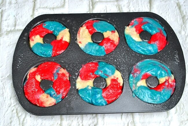 red white and blue swirled batter in a donut pan