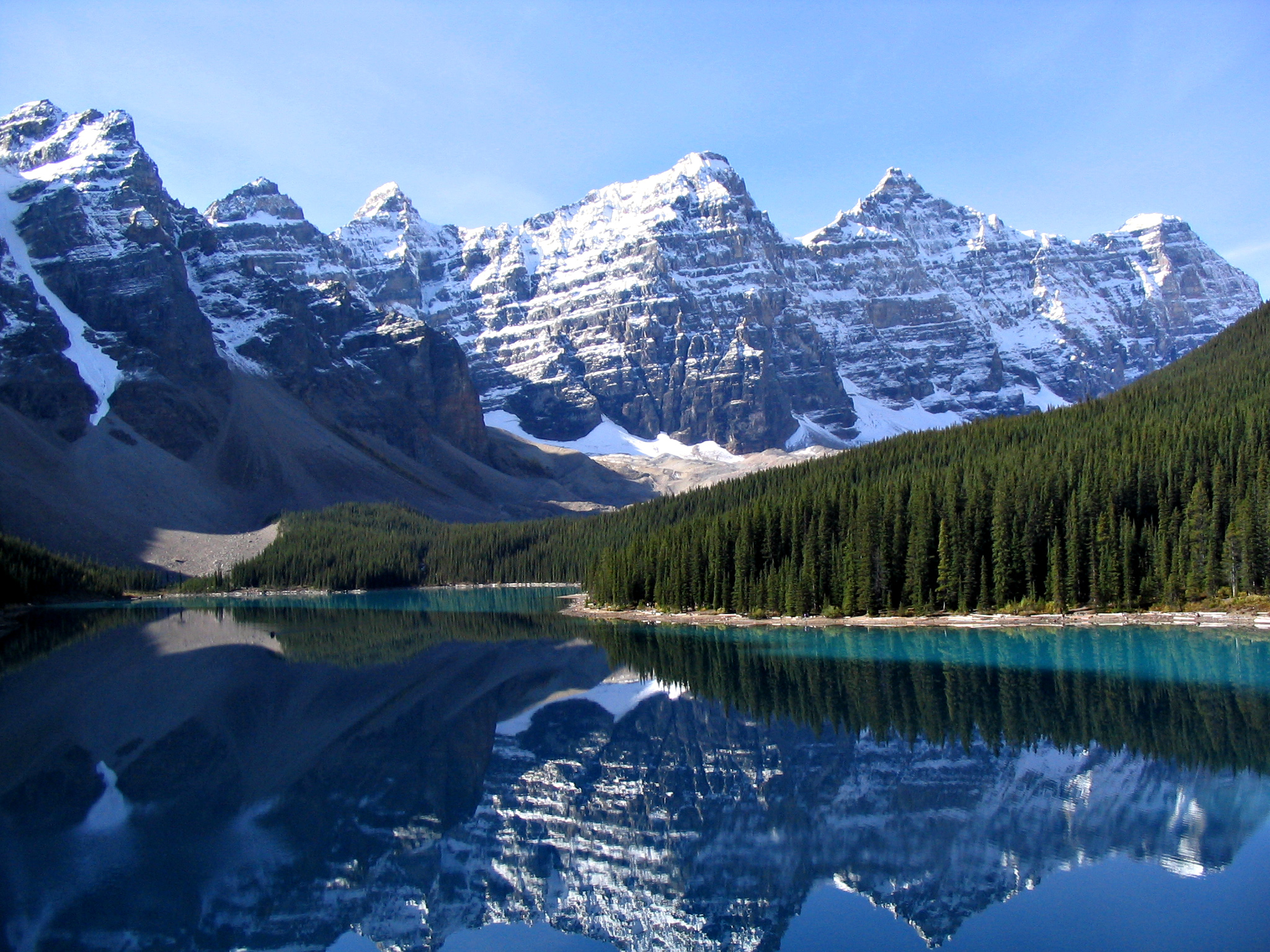 A view of Moraine Lake and the Valley of the Ten Peaks in Banff National Park. The smooth blue water of a lake is seen in the foreground, while snow-capped mountain peaks are visible in the distance.