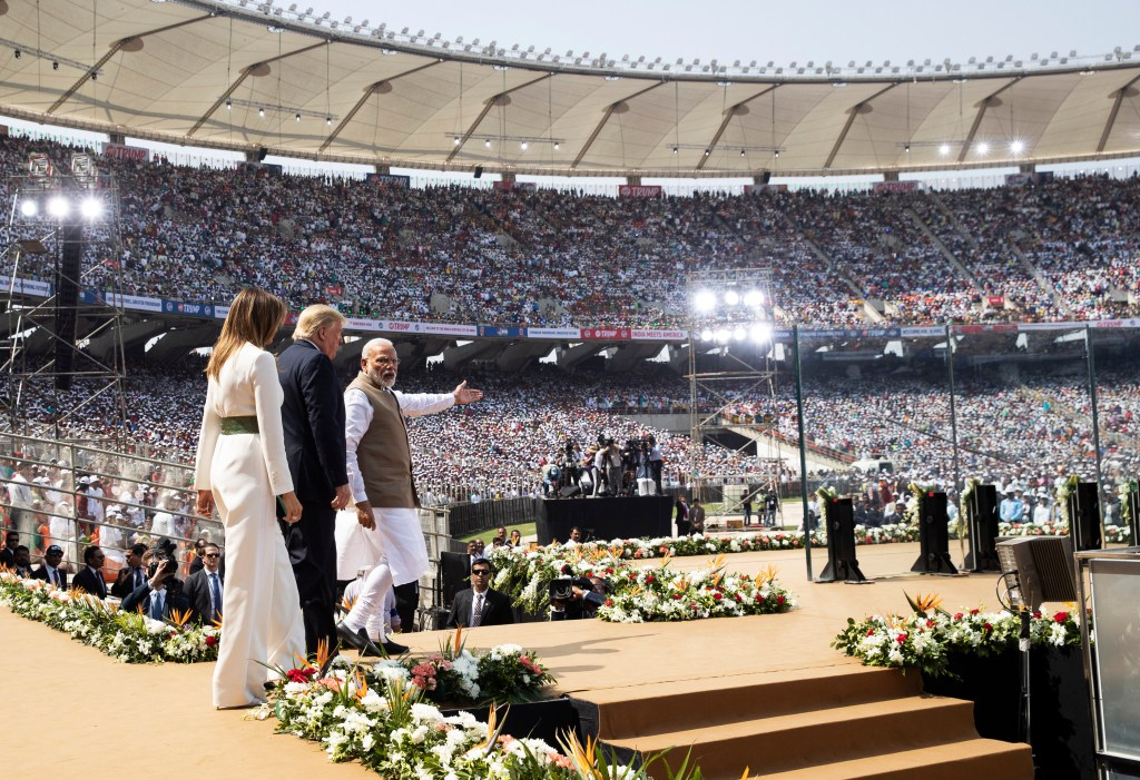 US President Donald Trump, first lady Melania Trump and Indian Prime Minister Narendra Modi at a cricket stadium, in Ahmedabad, India, in front of a large crowd of people.