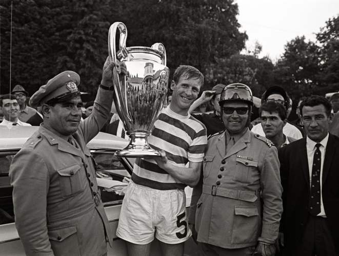 A soccer player in a striped jersey holds the European Cup trophy flanked by men on military uniforms on both sides