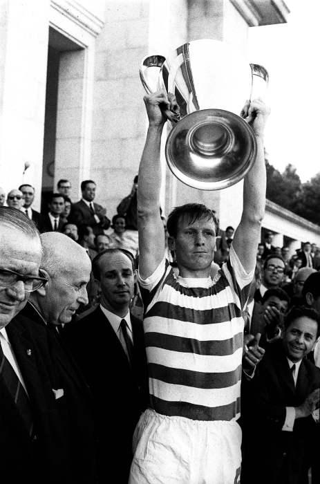 A soccer player in a striped Celtic jersey holds the European Cup trophy overhead with an expression of joy