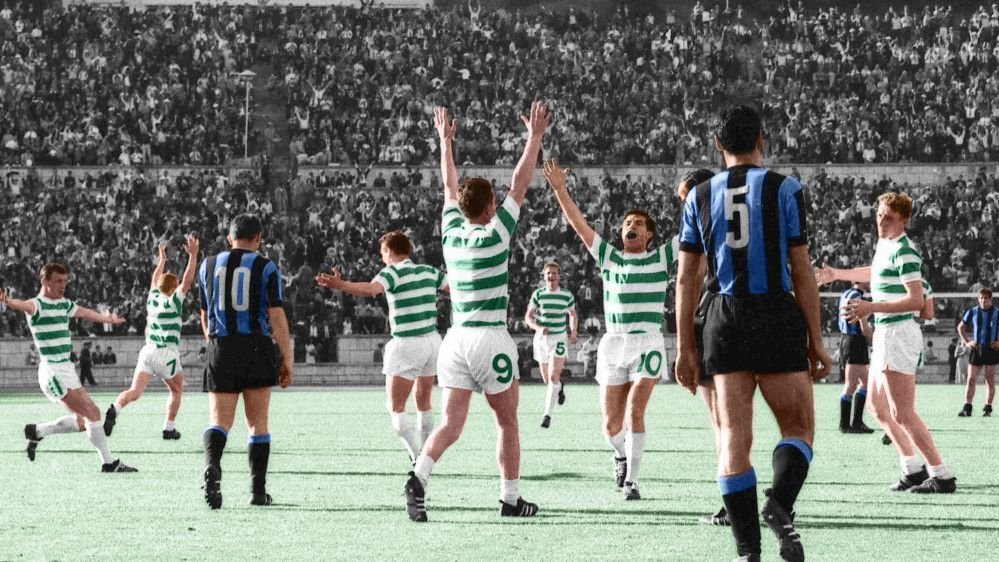 Celtic FC players in green and white striped jerseys raise their arms in celebration on a soccer field