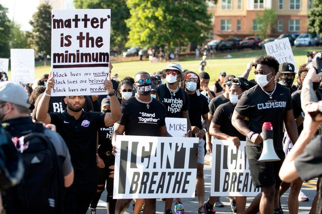 "A group of football players, predominately composed of Black men, march on the Clemson University campus. One holds a sign that reads ""matter is the minimum."" Two other men hold signs that read ""I can't breathe."""