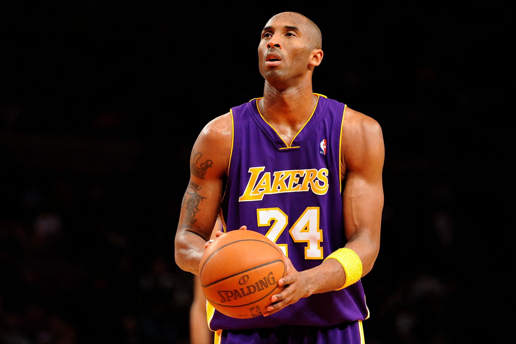 Basketball player Kobe Bryant holds a basketball at waist level while preparing to shoot a free throw.