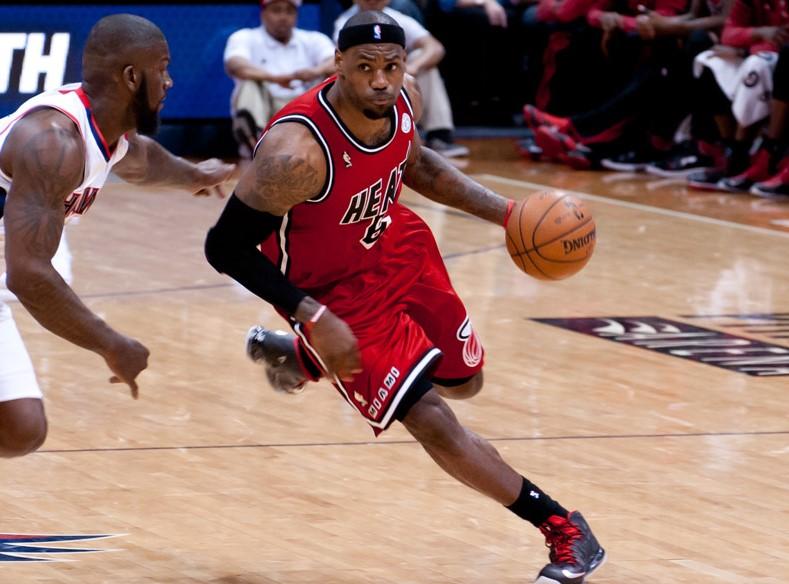 Lebron James, wearing a Miami Heat uniform, dribbles a basketball past a defender