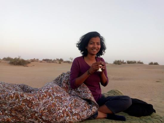 woman on bed in desert with tea in hand