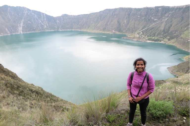 Girl in pink fleece jacket in front of a crater lake