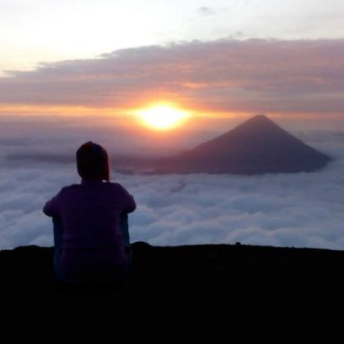 A girl looking at a mountain in distance with a cloud bed underneath. Rising sun in front.