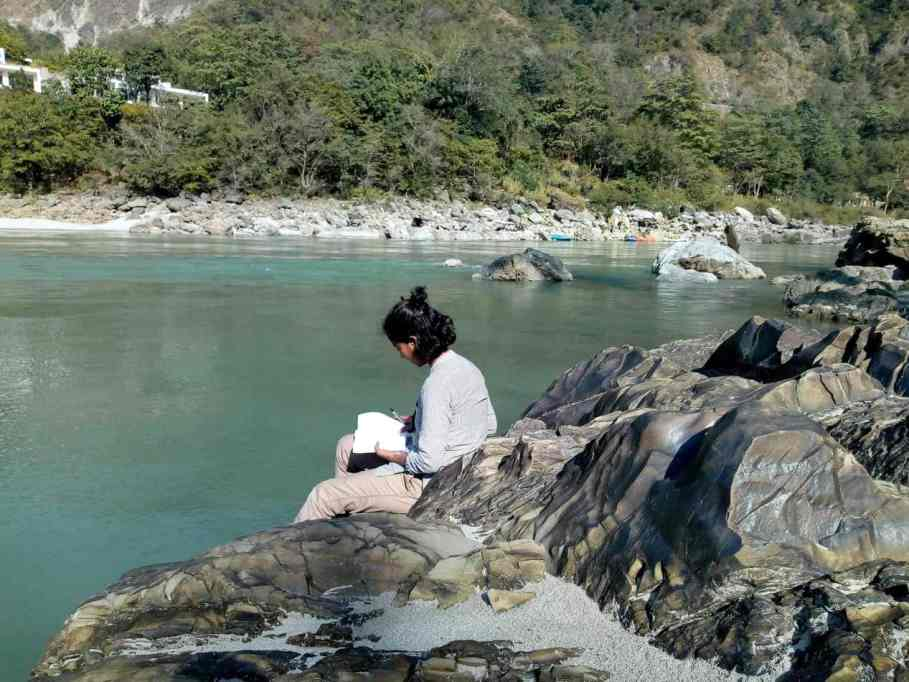 A woman Writing in a diary by Ganga River
