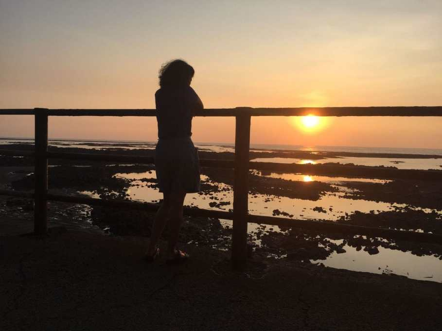 Girl overlooking sunset from a promenade