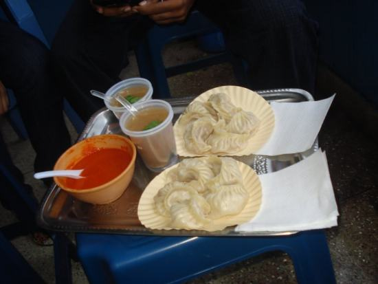 Steamed momos in two paper plates with red chutney and two glasses of beverage on a table