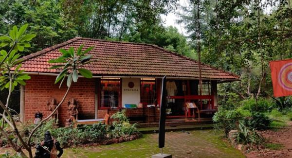 red brick house with red roof tiled roofs surrounded by trees in Auroville