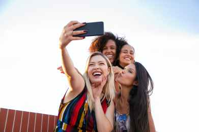 cheerful multiethnic girlfriends taking selfie on smartphone on sunny day