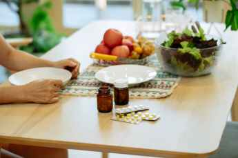 medicament and fresh fruits and veggies placed on table near unrecognizable person