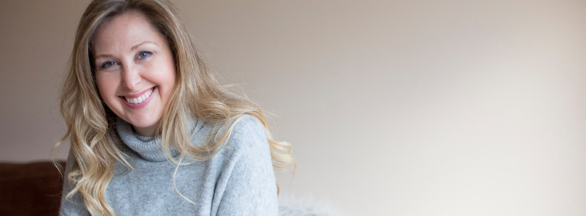 Lorraine Pannetier smiling profile photo with grey jumper, long blonde hair and blue eyes.