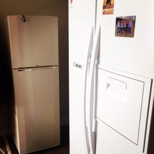 Our small fridge waving goodbye from the shadows of the newer bigger one.