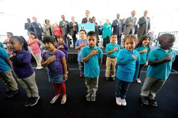 First graders from Science Center School lead officials in the Pledge of Allegiance. Photo: Gary Leonard