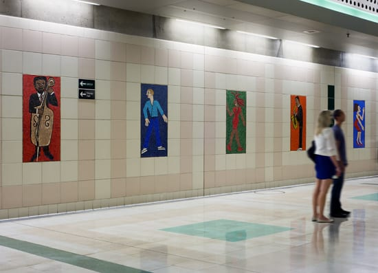 A view of one mezzanine wall at Civic Center Station picturing five of 52 individual glass mosaics comprising the artwork by Faith Ringgold titled People Portraits: in Creativity, Performing, Sports and Fashion.