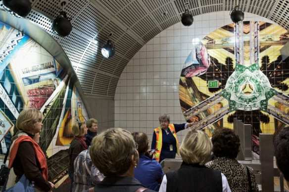A Metro Art tour guide discusses the artwork at North Hollywood Station. The ceramic mural by Anne Marie Karlsen, called Kaleidoscope Dreams, depicts the dreams and aspirations of generations of San Fernando Valley immigrants and celebrates the Valley's spirit and history.