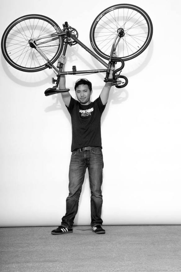 Alan holding his fixed gear bicycle over his head.
